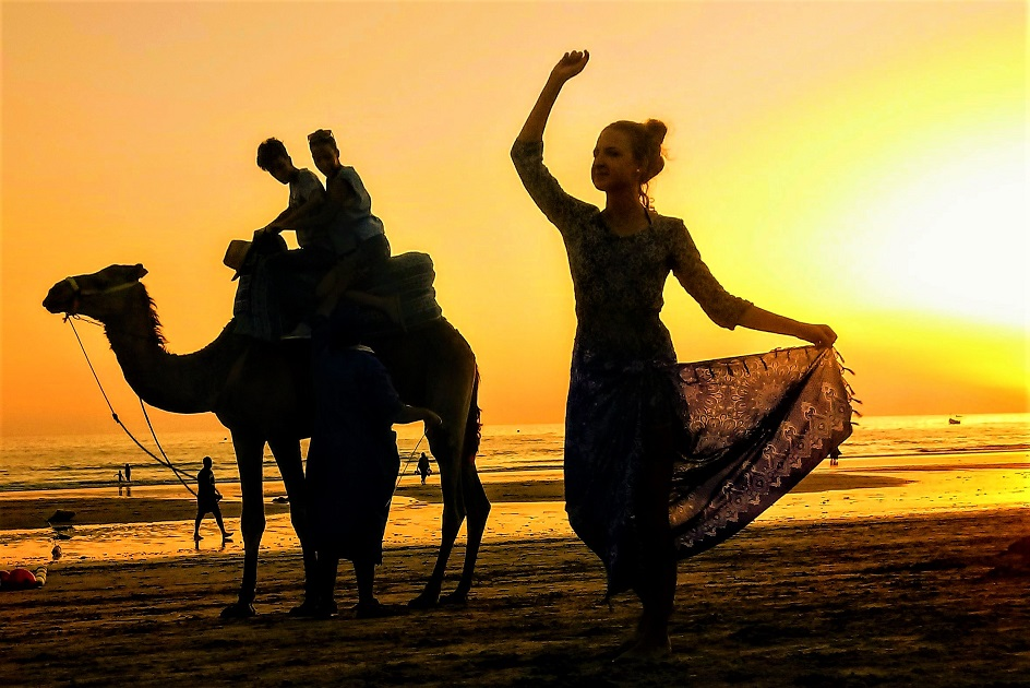 Moroccan woman on the beach with a camel in the background